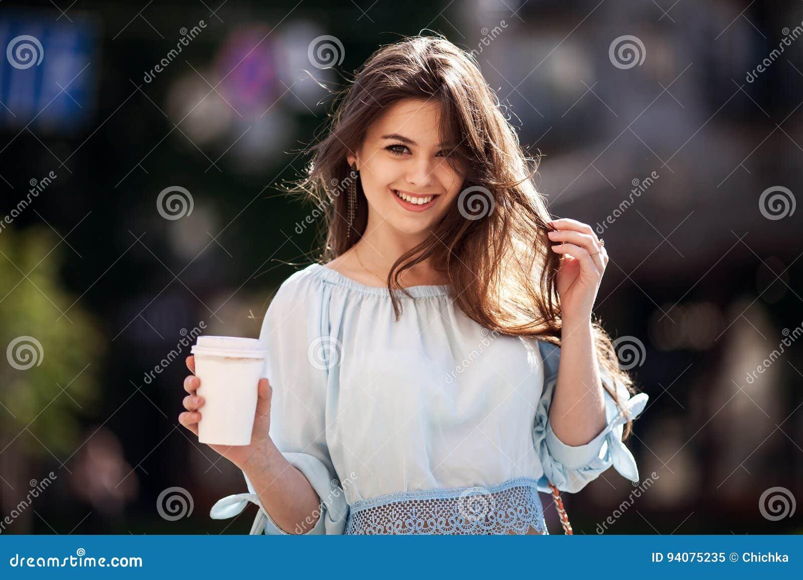 Sluit omhoog de stijlportret van de manierstraat van een mooi meisje in een toevallige uitrustingsgangen in de stad Het mooie bru