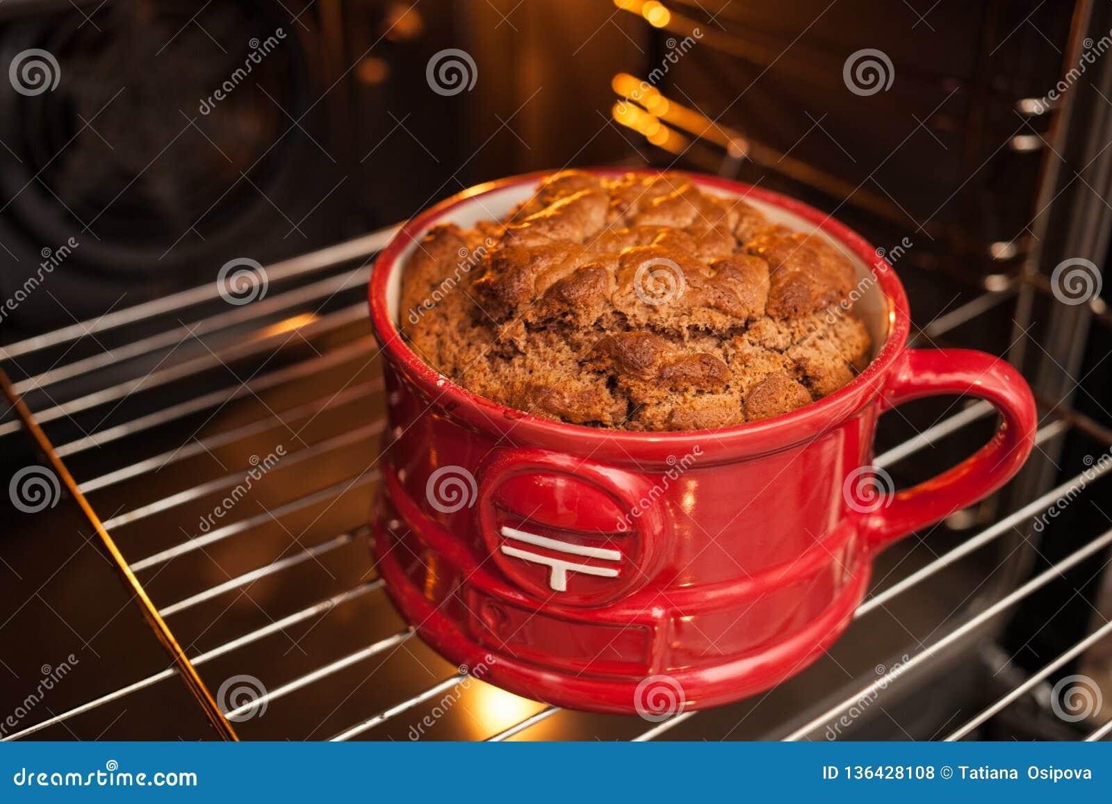 Sluit omhoog een grote weelderige blozende mugcake in een rode die mok in de oven wordt gekookt Het koken en cupcake receptenreal