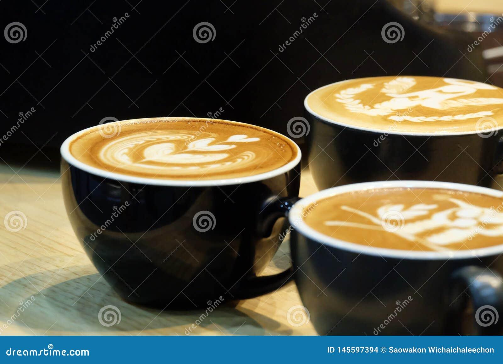 Sluit omhoog een mooie lattekunst bovenop een hete lattekoffie in een zwarte kop