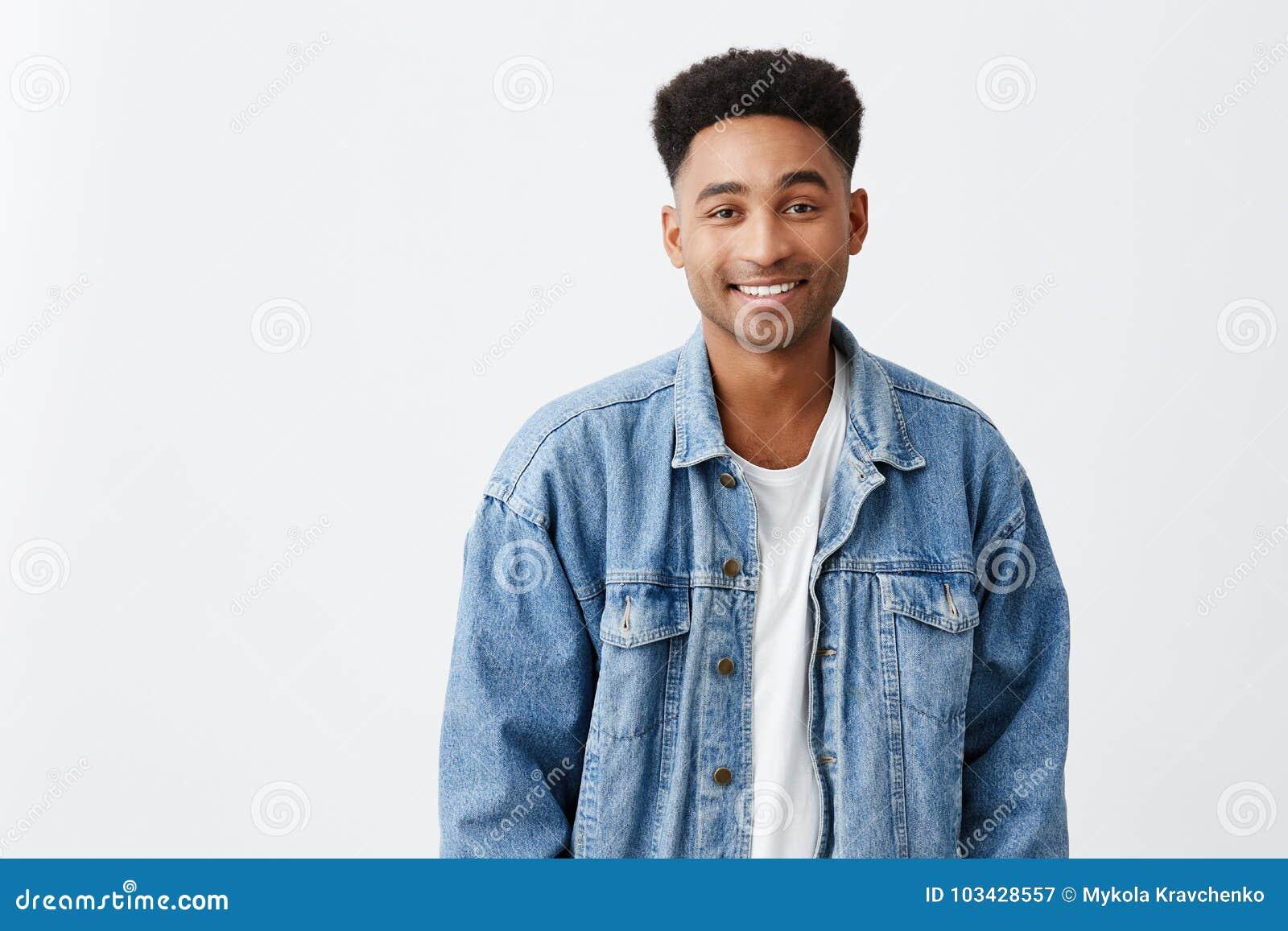 Sluit omhoog geïsoleerd op wit portret van jonge mooie vrolijke donker-gevilde mannelijke universitaire student met afrokapsel