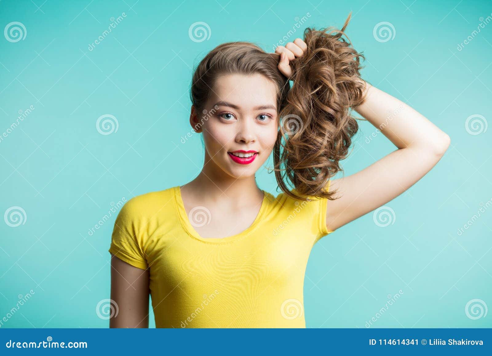 Sluit omhoog geschoten van het modieuze jonge vrouw glimlachen tegen blauwe achtergrond Het mooie vrouwelijke model verzamelde ha