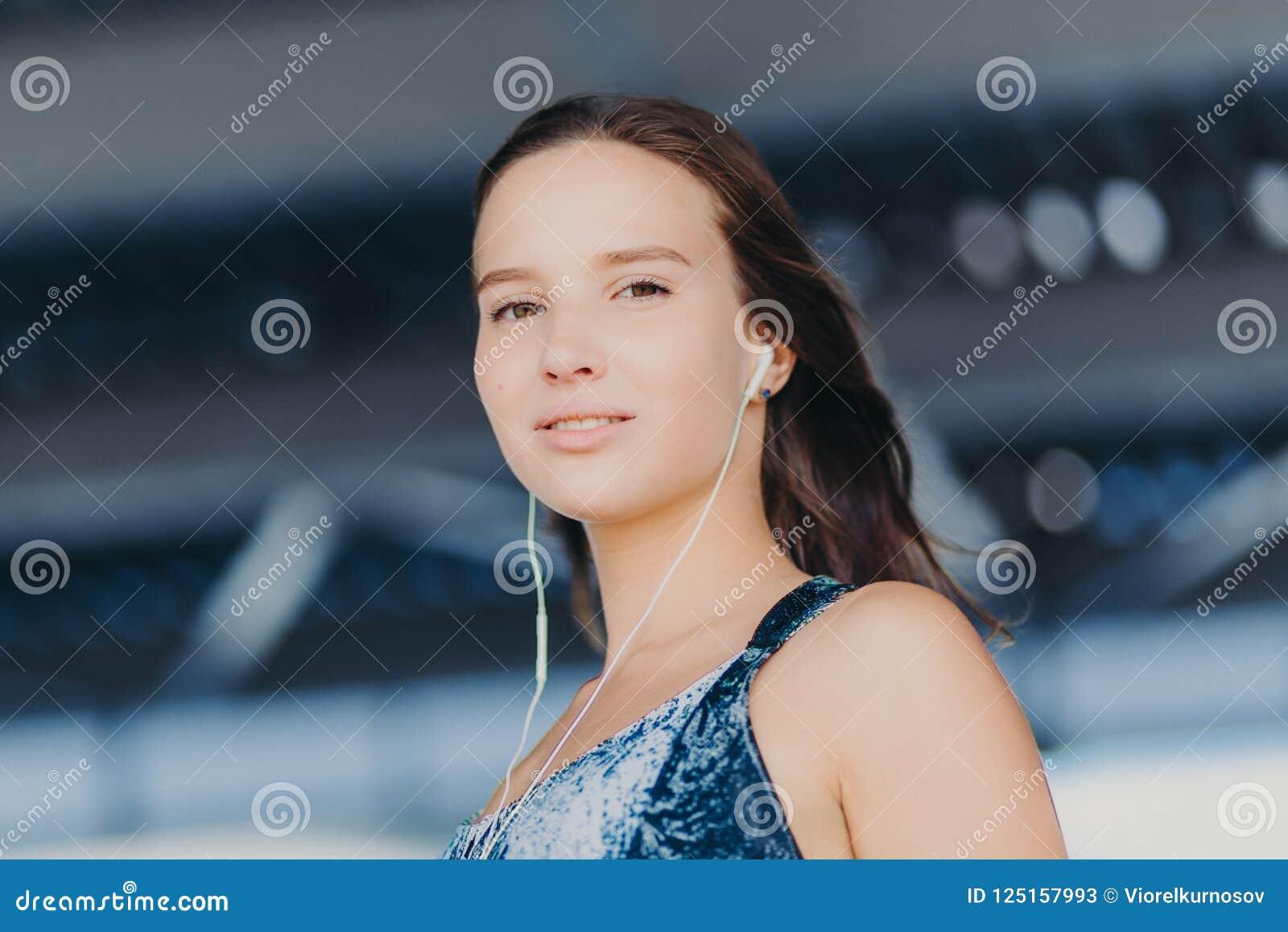 Sluit omhoog geschoten van knappe gezonde Europese vrouw luistert muziek met onherkenbaar apparaat, bekijkt direct camera, stelt