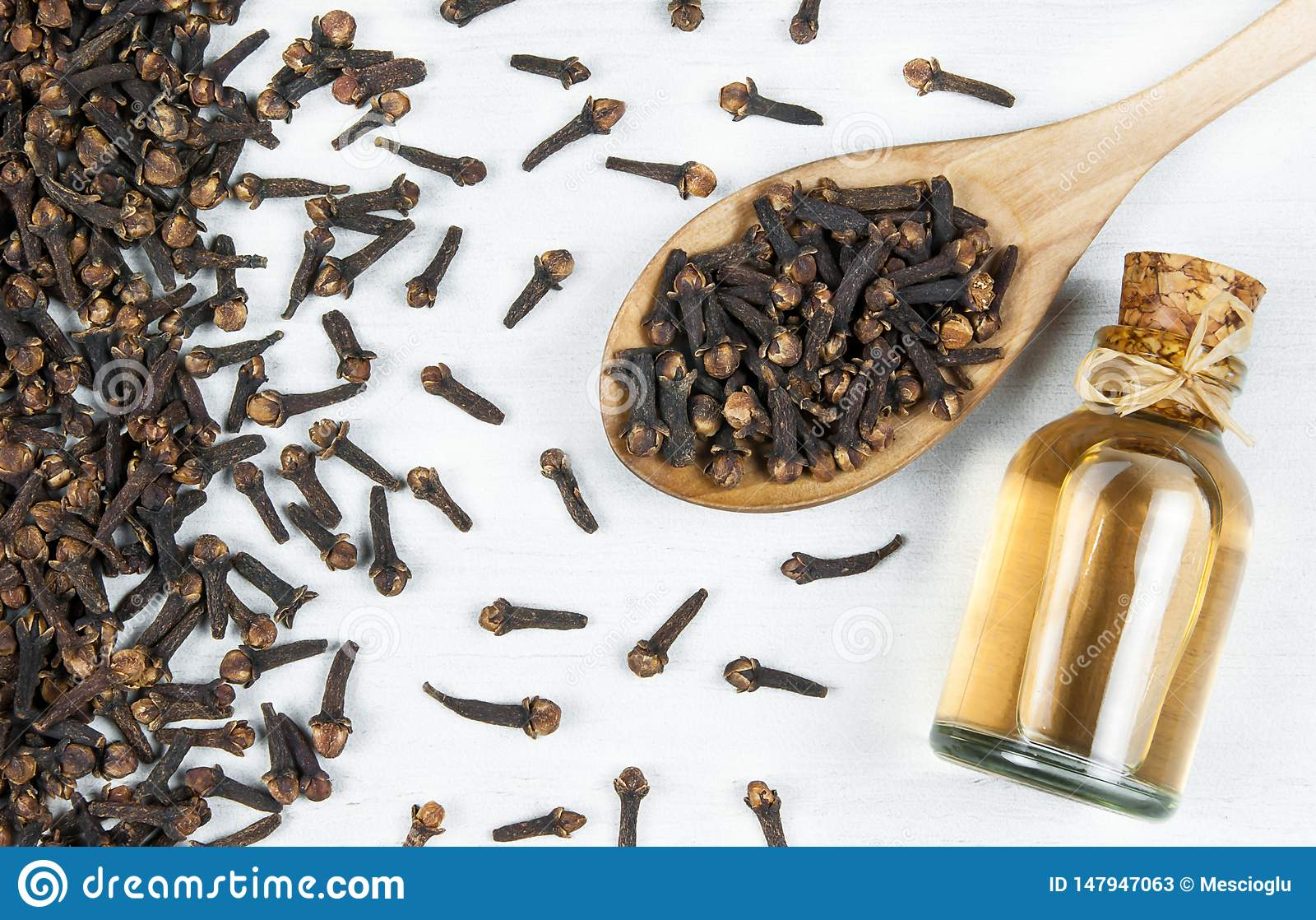 Sluit omhoog glasfles van kruidnagelolie en kruidnagels in houten lepel op witte rustieke lijst