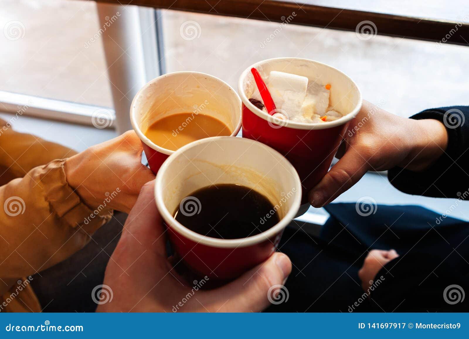 Sluit omhoog handen met koffiekoppen in toejuichingentijd de vrienden hebben pret en drinken koffie in de cafetaria