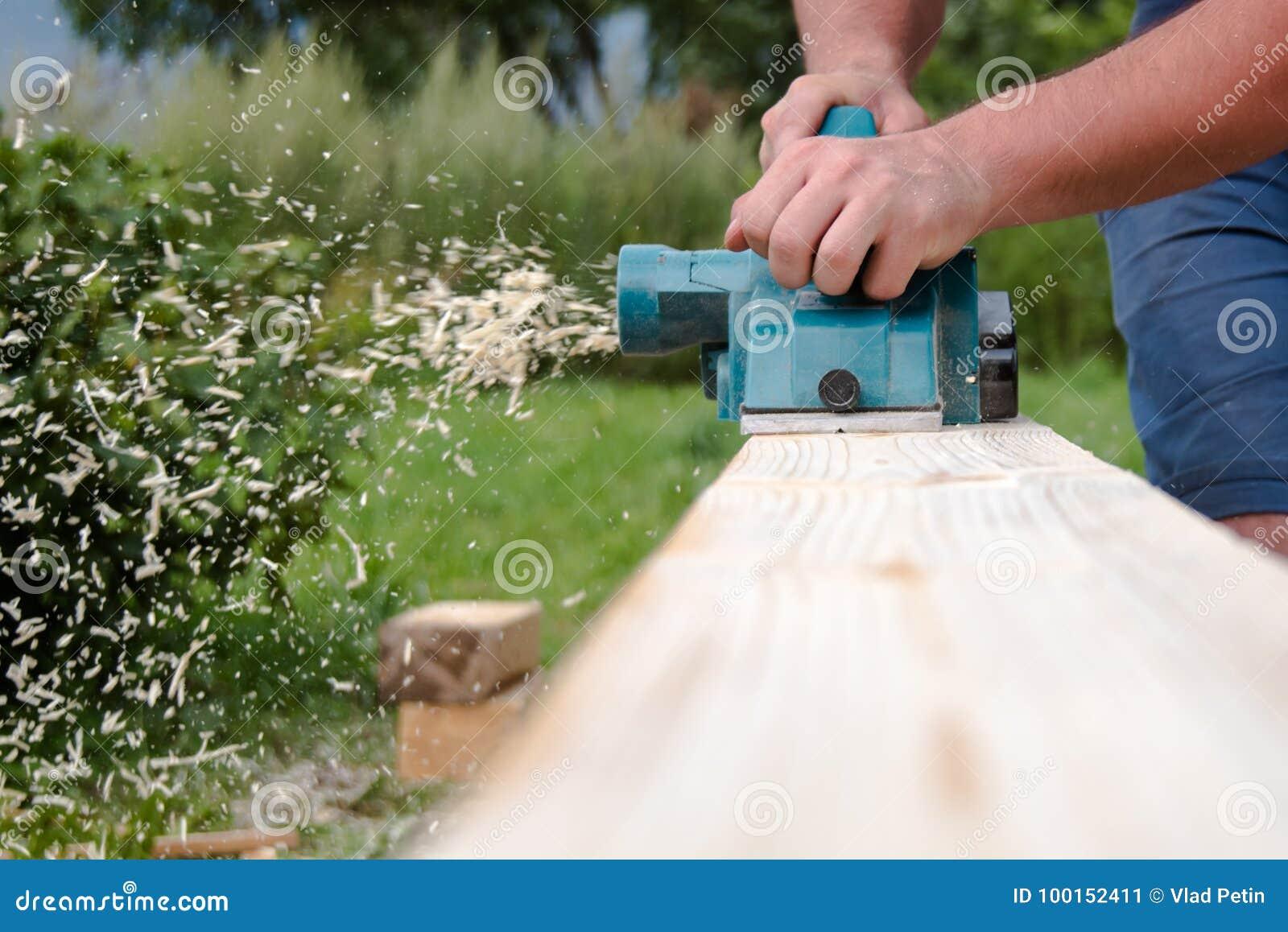 Sluit omhoog handen van timmerman die met elektrische planer aan houten plank werkt