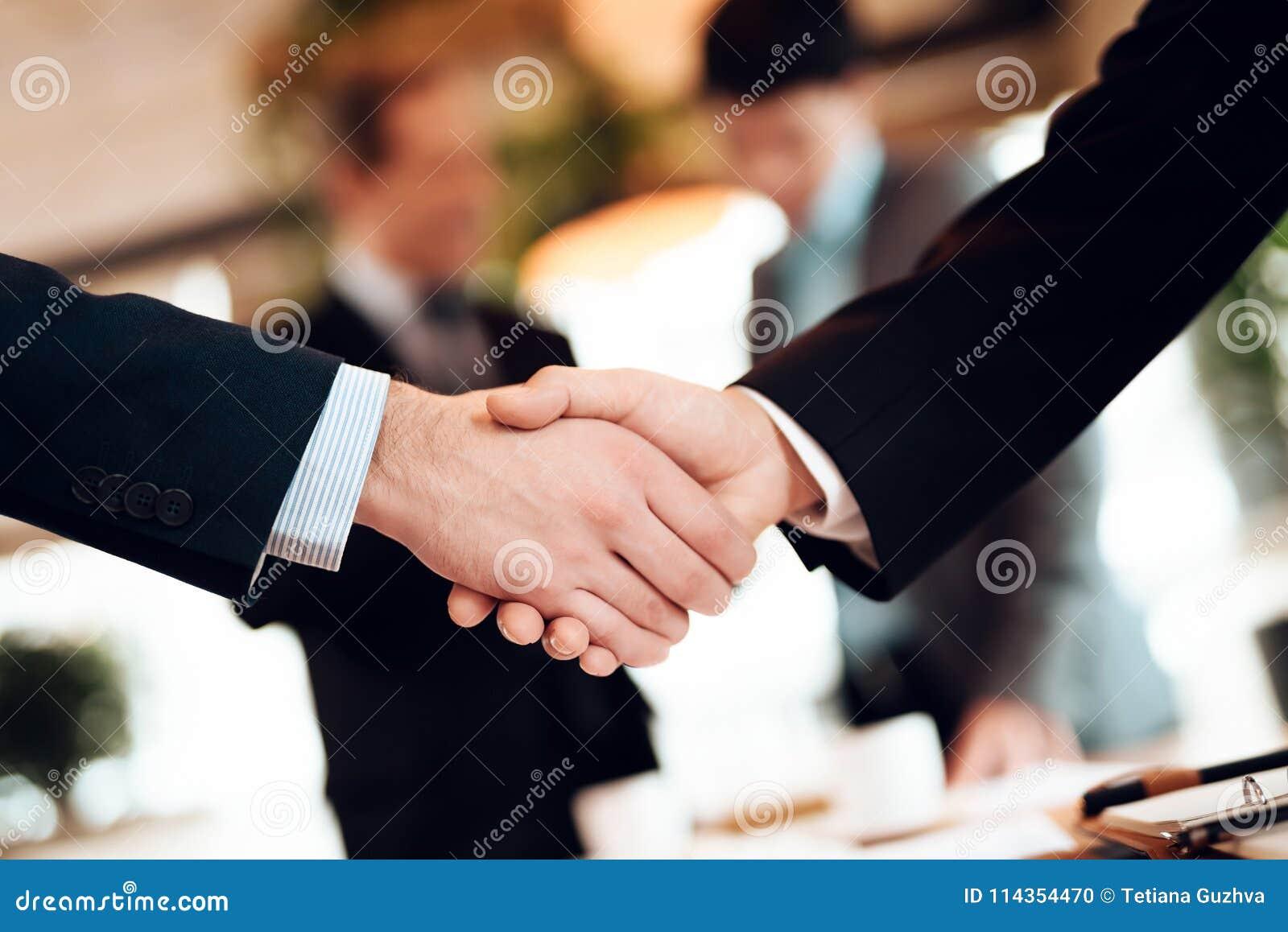 Sluit omhoog het samenkomen Chinese zakenlieden in restaurant De mensen schudden handen