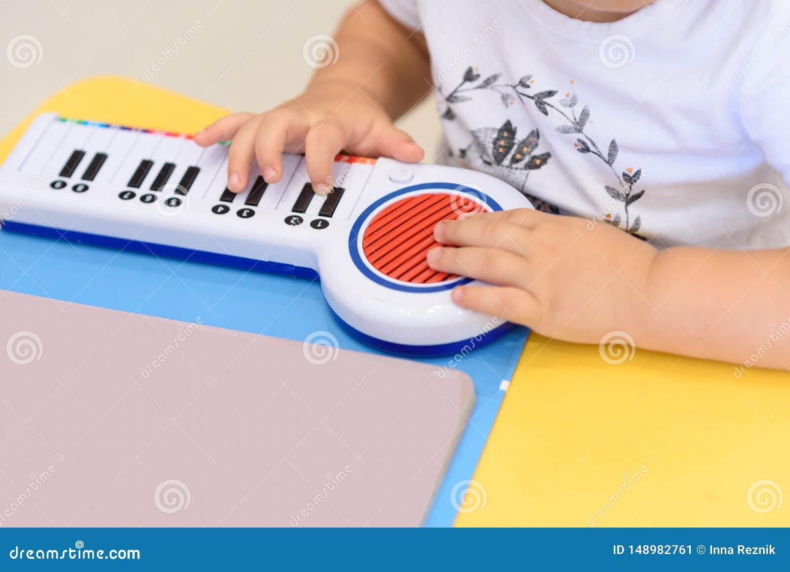 Sluit omhoog kleine handenspelen op een stuk speelgoed piano