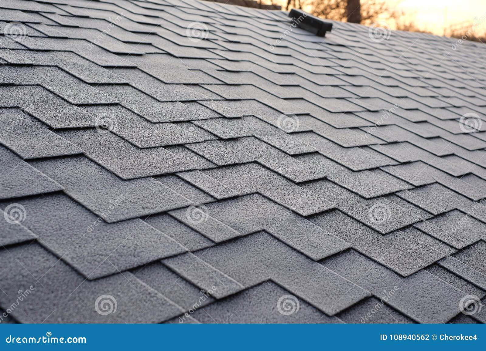 Sluit omhoog mening over Asphalt Roofing Shingles Background Dakdakspanen - Dakwerk De schade van het dakspanendak met vorst word