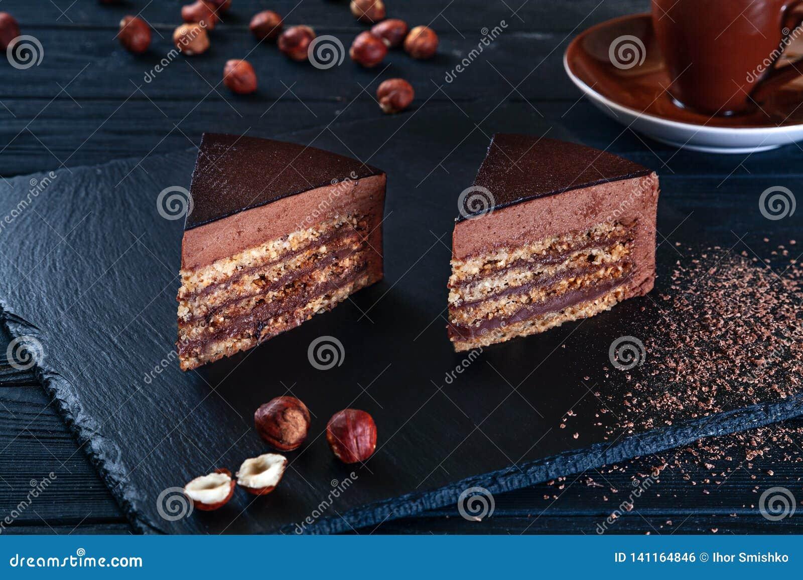 Sluit omhoog mening over gesneden hazelnootcake met cacao op een zwarte achtergrond en een plaat