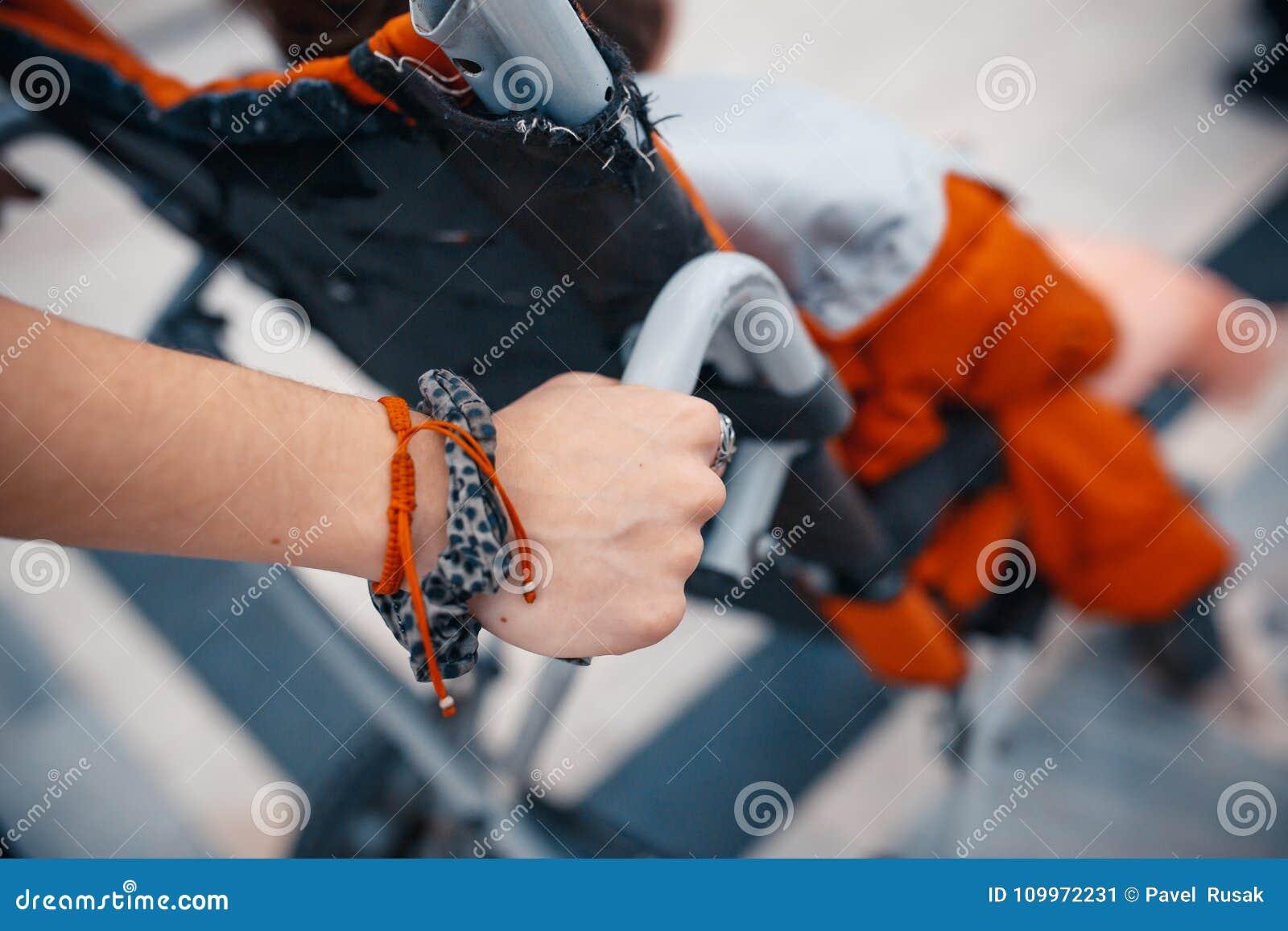Sluit omhoog mening van de handen van een vrouw die een gehandicapte man binnen duwen