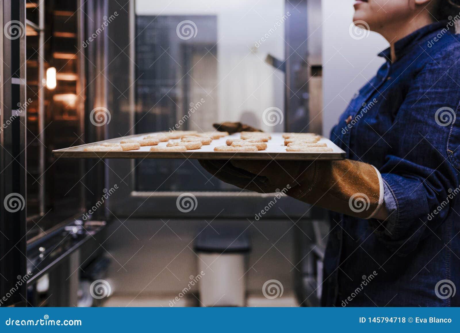 Sluit omhoog mening van de holdingsrek van de vrouwenholding van snoepjes in een bakkerij