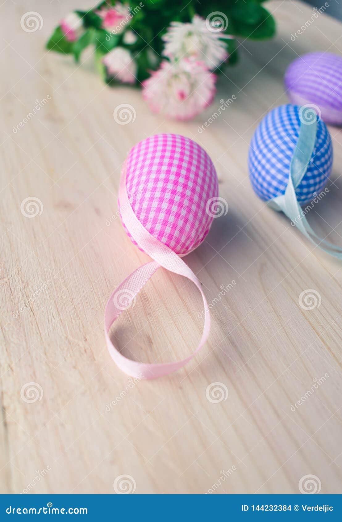 Sluit omhoog mening van roze en blauwe geruite paaseierendecoratie en witte en roze madeliefjes op bleke houten achtergrond