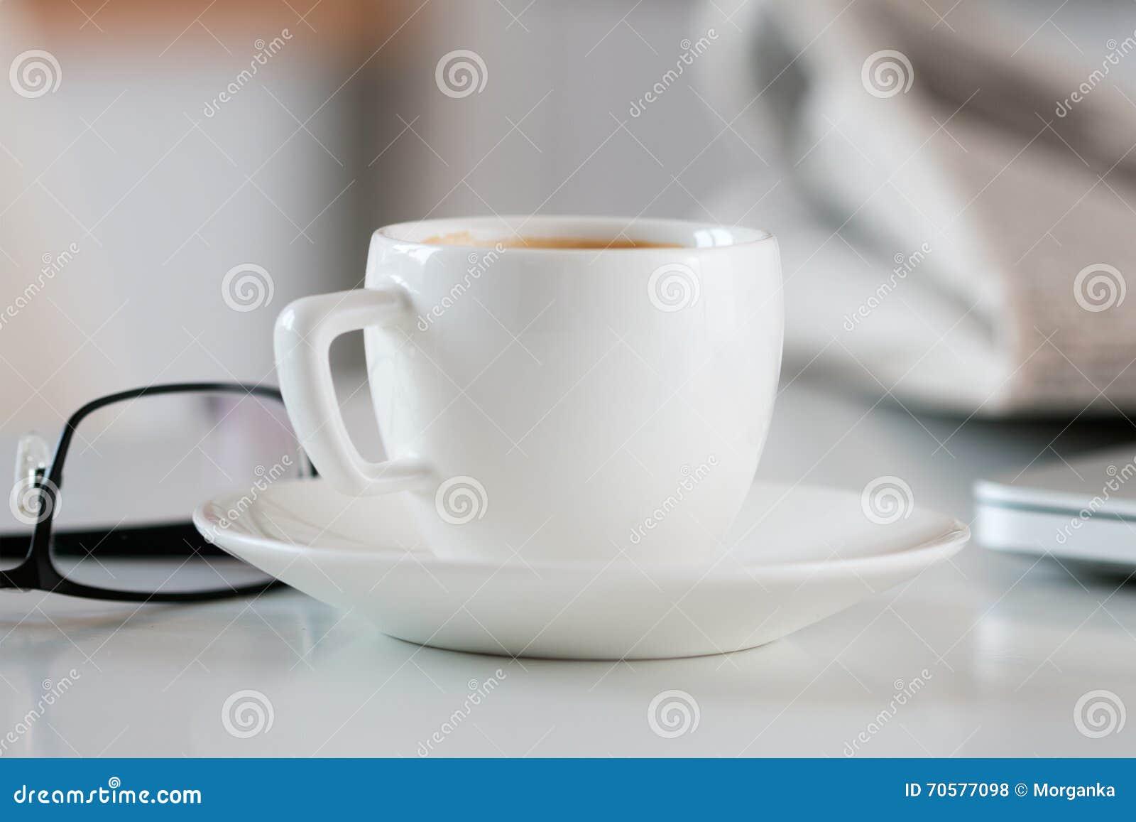 Sluit omhoog mening van witte koffiekop op lijst met glazen en nieuws