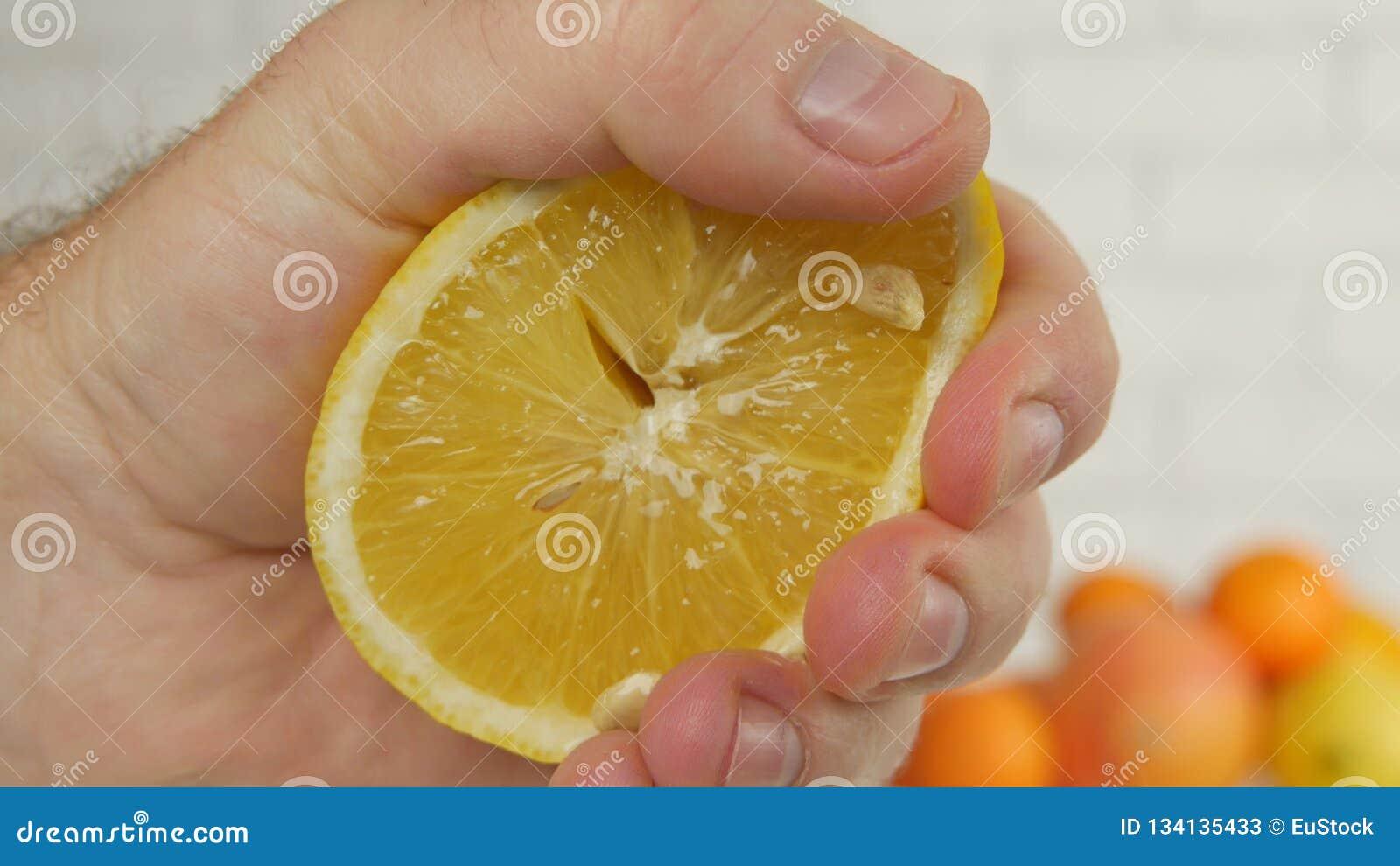 Sluit omhoog Mensenhand Drukkend een Zoet en Sappig Oranje Fruit