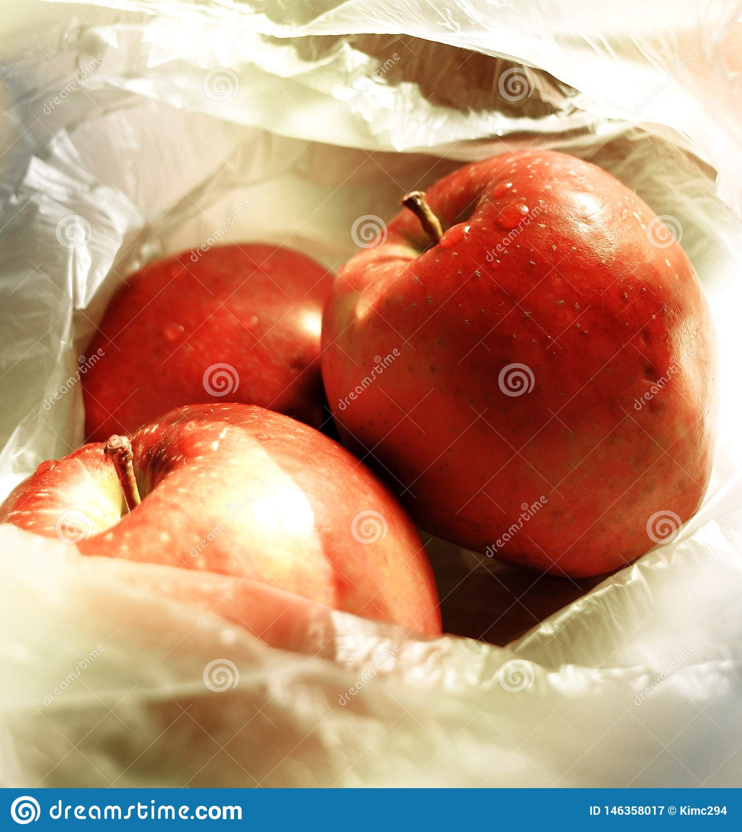 Sluit omhoog op drie rode appelen liggend in een transparante dunne plastic zak