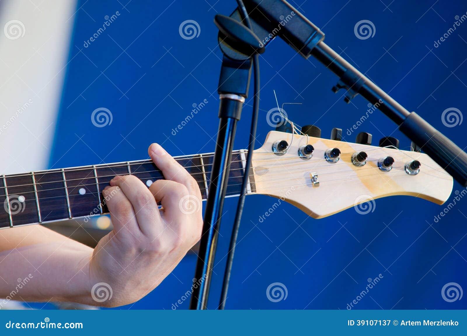 Sluit omhoog op mensen` s hand het spelen gitaar