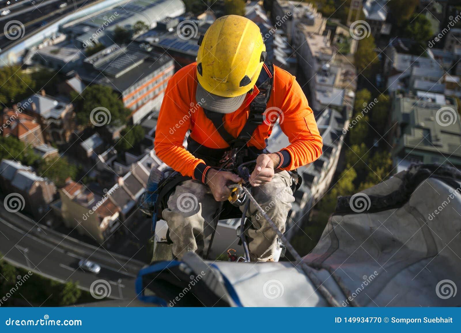 Sluit omhoog pic van mannelijke de banenarbeider die van de kabeltoegang gele bouwvakker, lang kokeroverhemd dragen, veiligheidsu