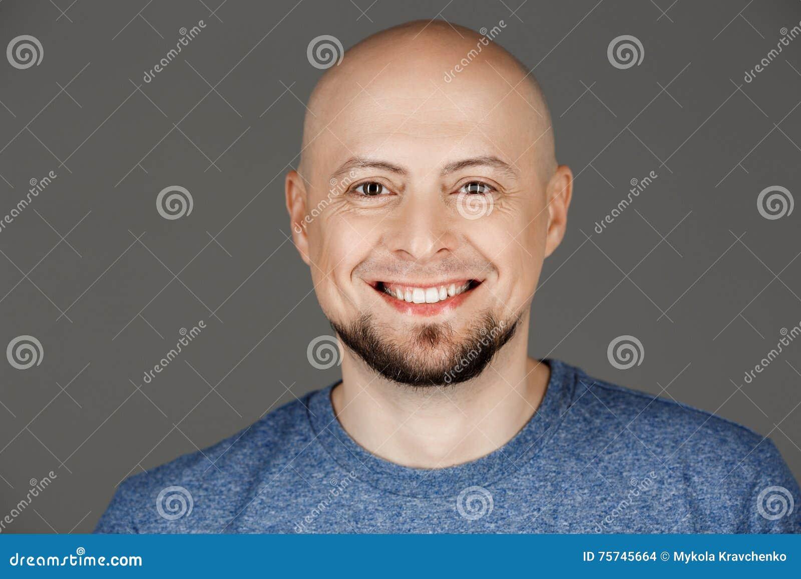 Sluit omhoog portret van de knappe mens die op middelbare leeftijd in grijs overhemd bij camera over donkere achtergrond glimlach