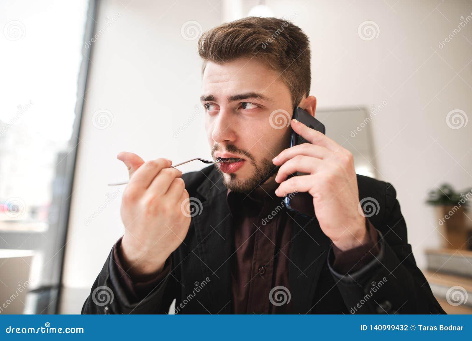 Sluit omhoog portret van een bedrijfsmensenzitting in een lichte koffie, sprekend op de telefoon, etend een voedselvork en weg ki
