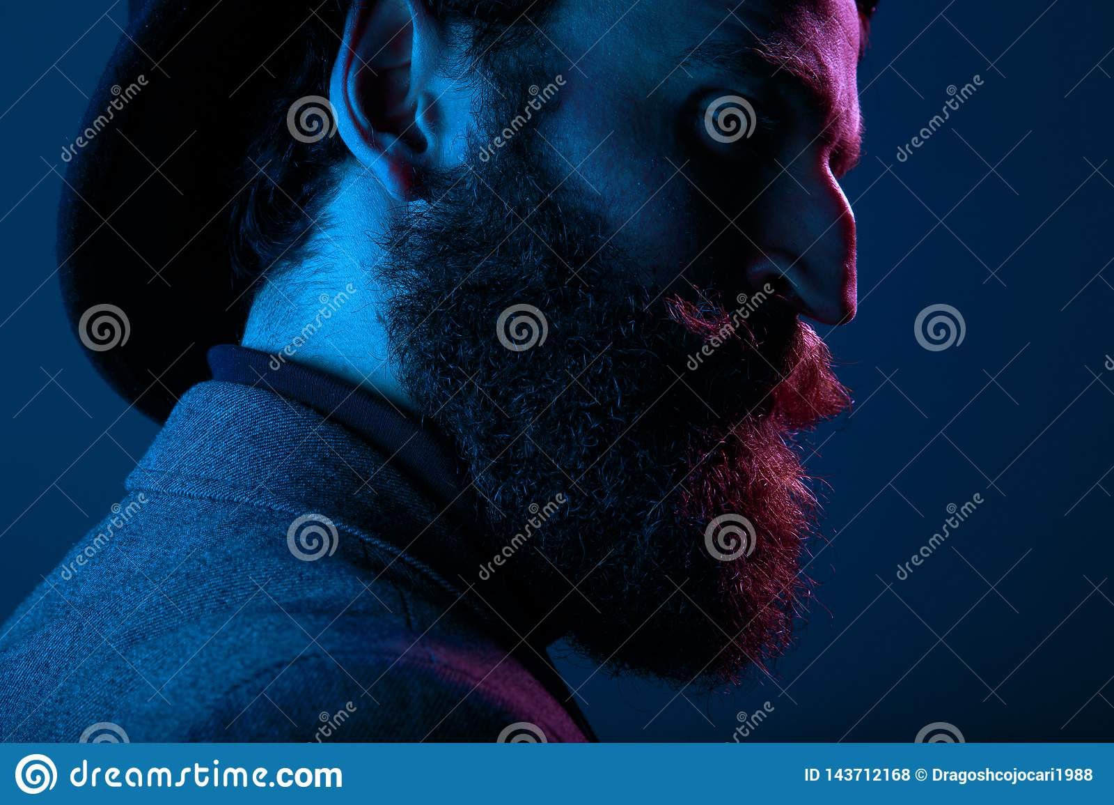 Sluit omhoog portret van een gebaarde mens in elegante hoed en kostuum, die in profiel in studio stellen, op blauwe achtergrond w