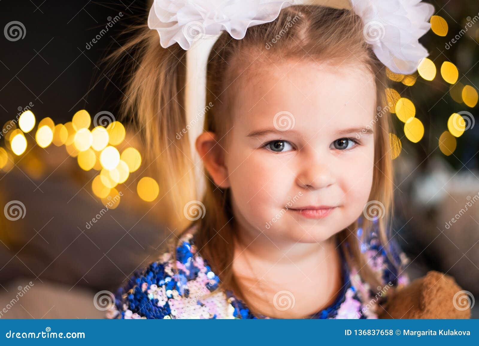 Sluit omhoog portret van een jong meisje met a buigt op haar haar