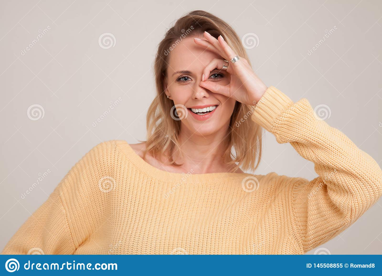 Sluit omhoog portret van glimlachende blondevrouw die met witte tanden, de camera door vingers in o.k. gebaar bekijken Geel drage