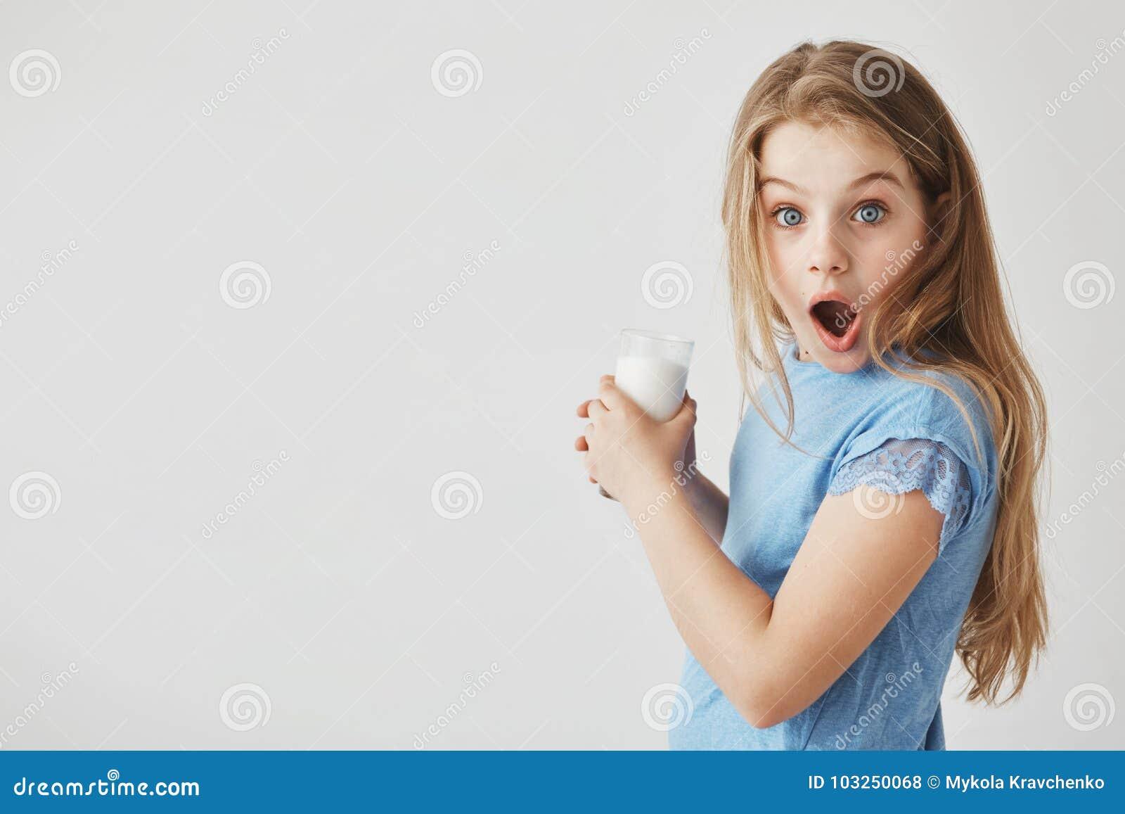 Sluit omhoog portret van grappig knap meisje die met licht haar in camera met geschokte uitdrukking, het houden kijken