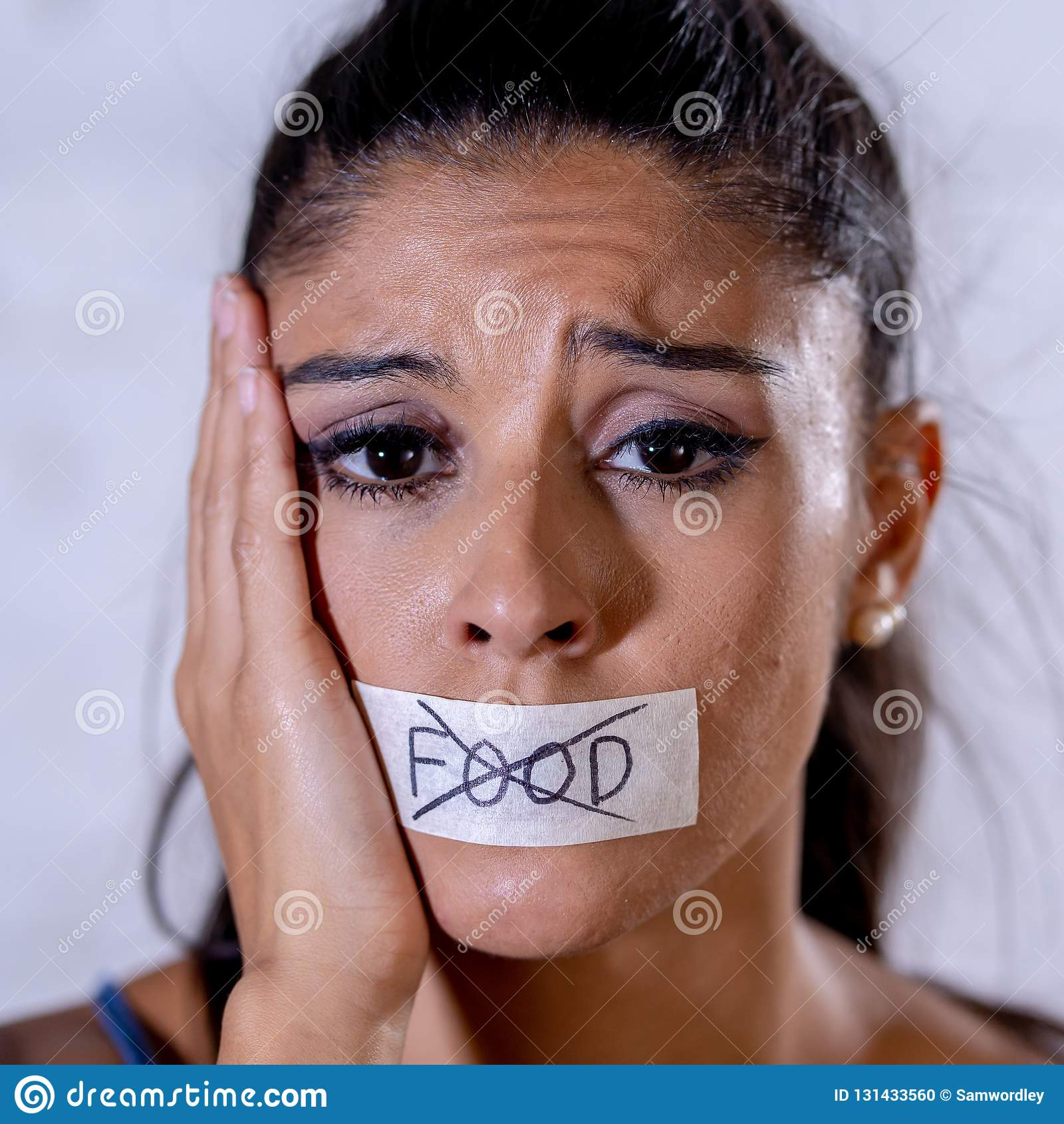 Sluit omhoog portret van jonge aantrekkelijke Latijnse die vrouw met mond op stokband met tekst geen voedsel in dieetanorexie het