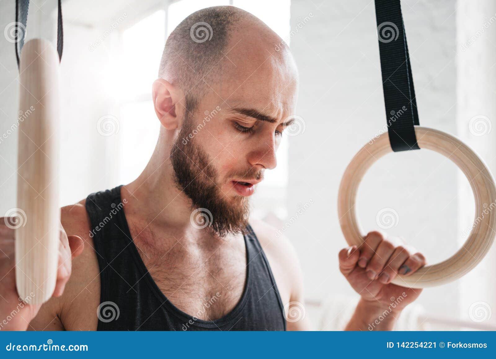 Sluit omhoog portret van turnermannetje die rust na de intense training van de onderdompelingsring nemen bij gymnastiek