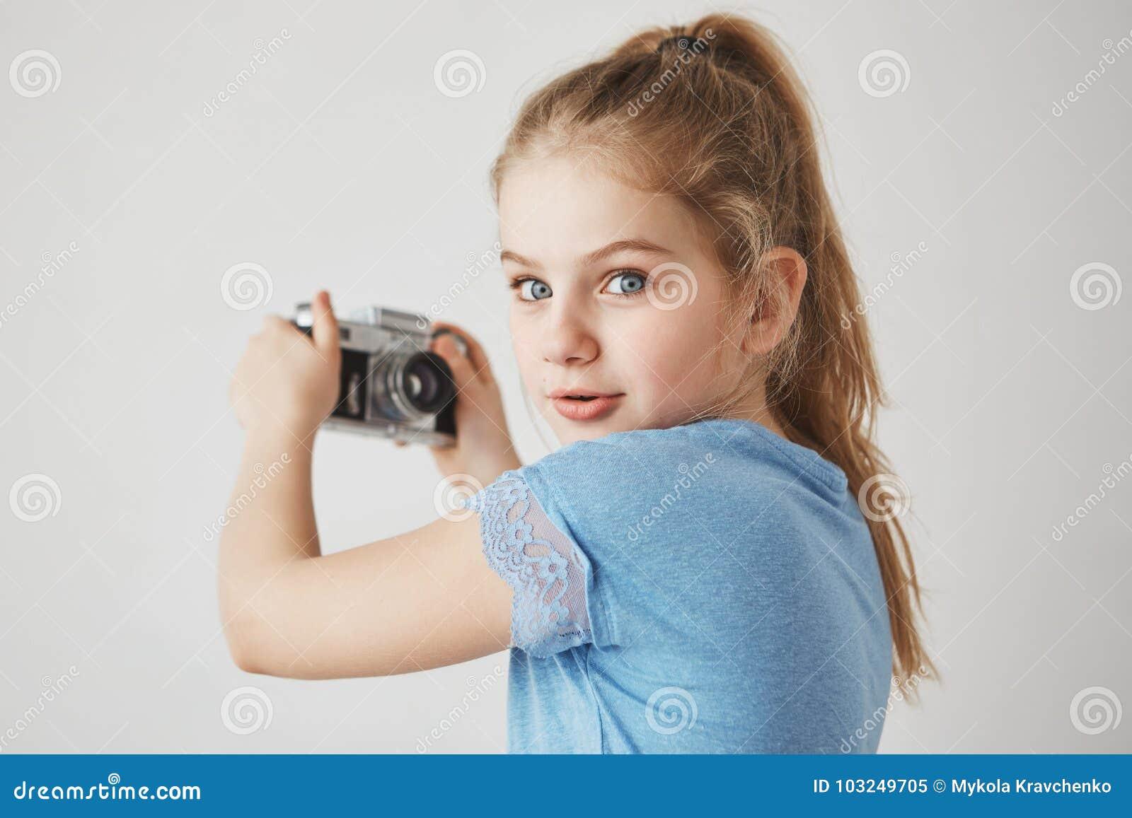 Sluit omhoog portret van vrolijk leuk meisje die met blondehaar en blauwe ogen, in camera met geinteresseerde uitdrukking kijken