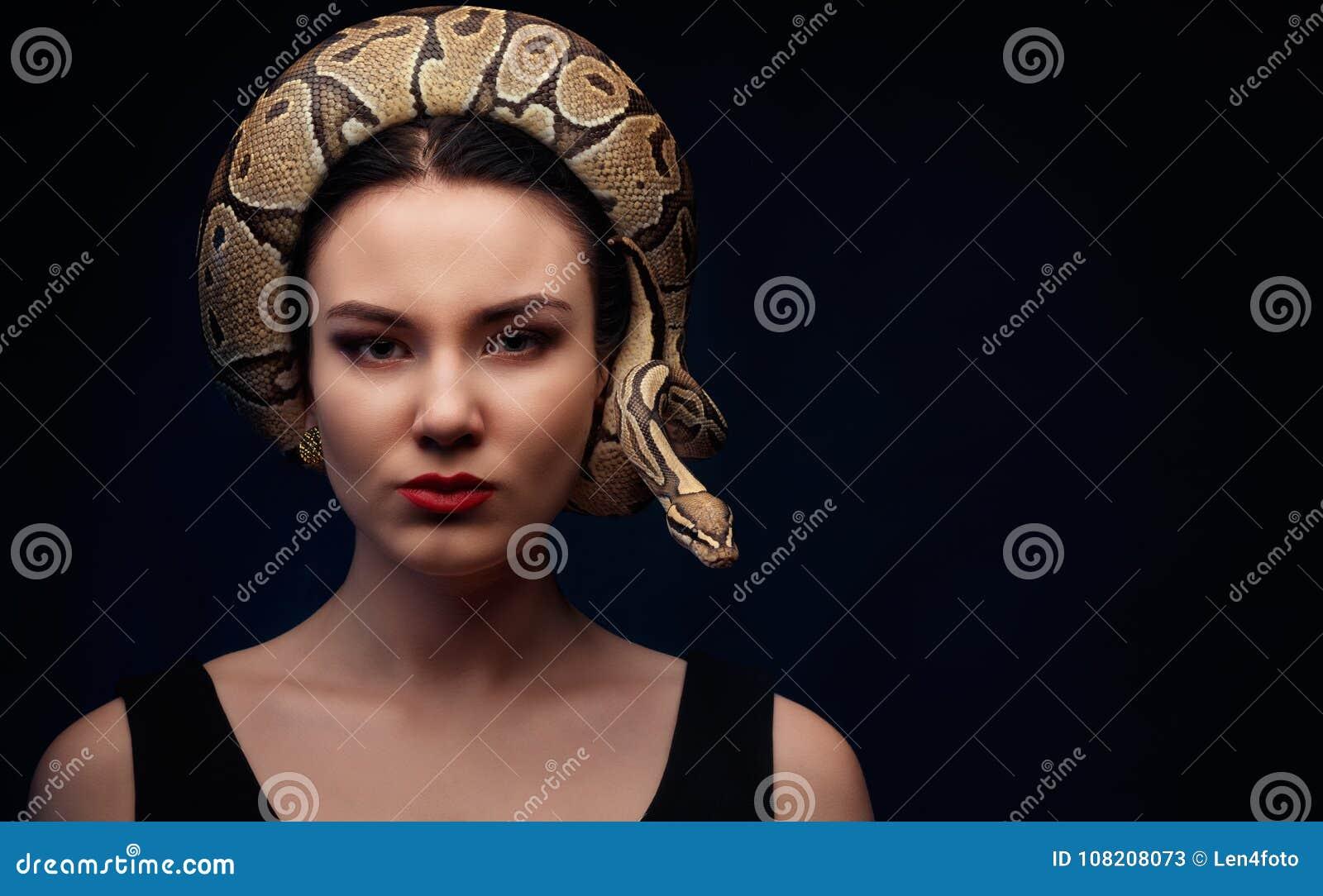 Sluit omhoog portret van vrouw met slang rond haar hoofd op donkere bedelaars