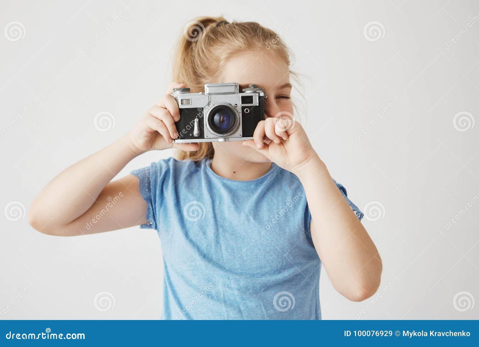 Sluit omhoog portret van weinig aanbiddelijk meisje met blondehaar in blauwe t-shirt die een beeld van vrienden in school gaan ne
