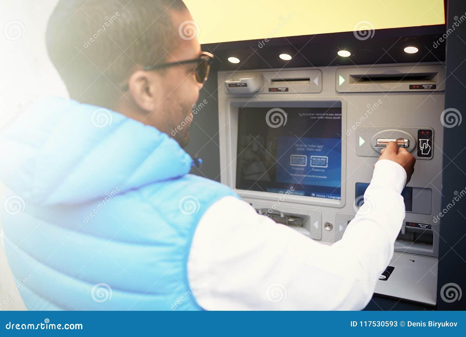 Sluit omhoog profielportret van zwarte mensentoerist gebruikend ATM-machine, na wenken in vreemde taal op het zijn scherm