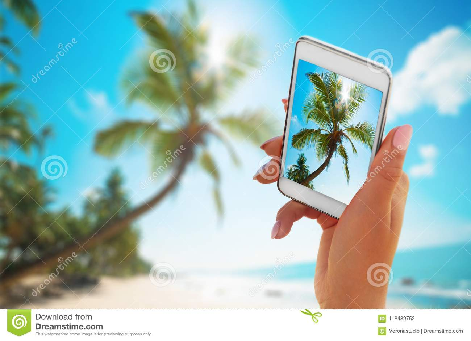 Sluit omhoog smartphone van de handholding op de zomerstrand technologie, reis, toerisme, mededeling en mensenconcept