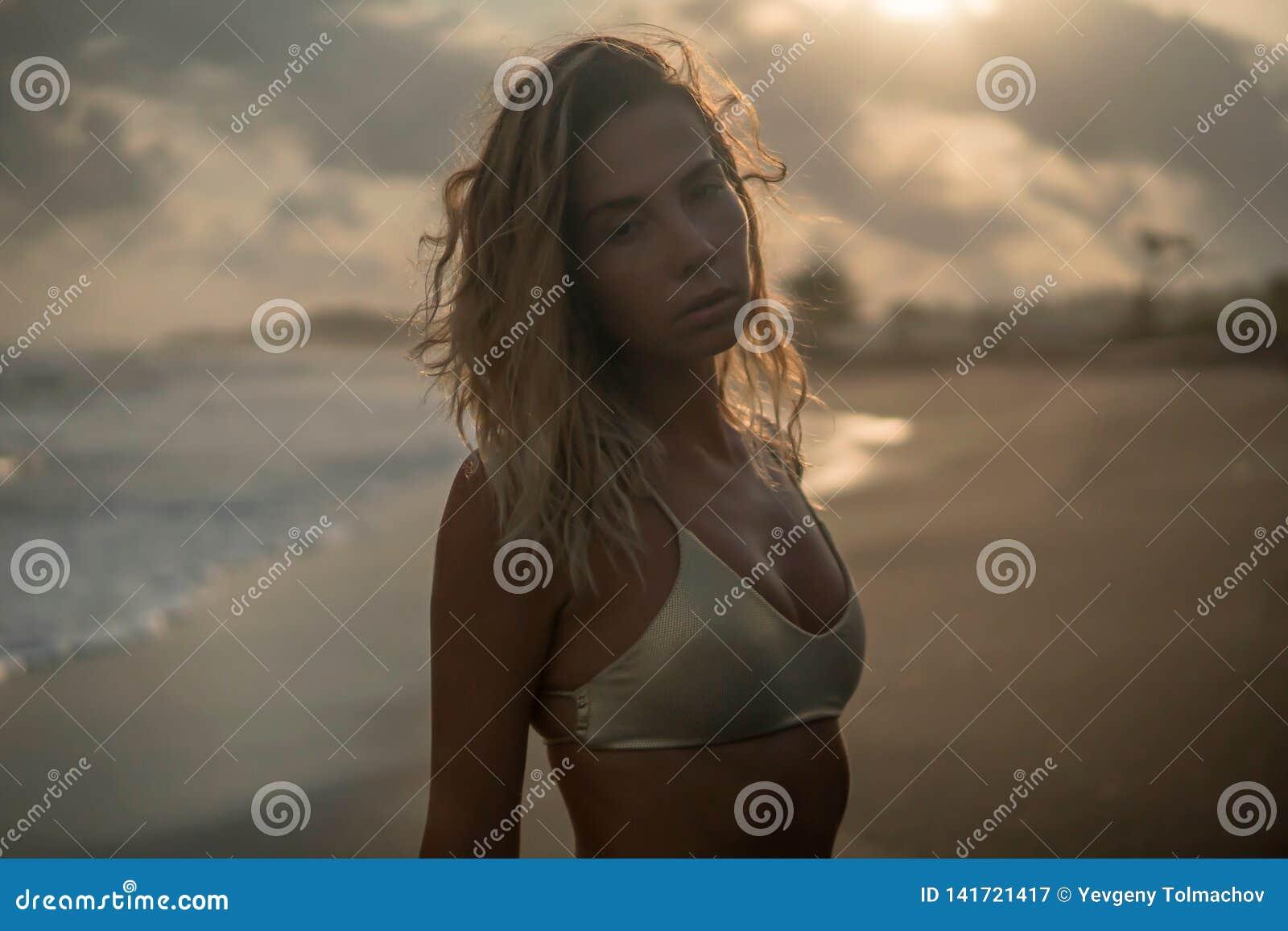 Sluit omhoog van aardige jonge vrouw in het gouden bikini stellen door oceaan bij de tropische toevlucht