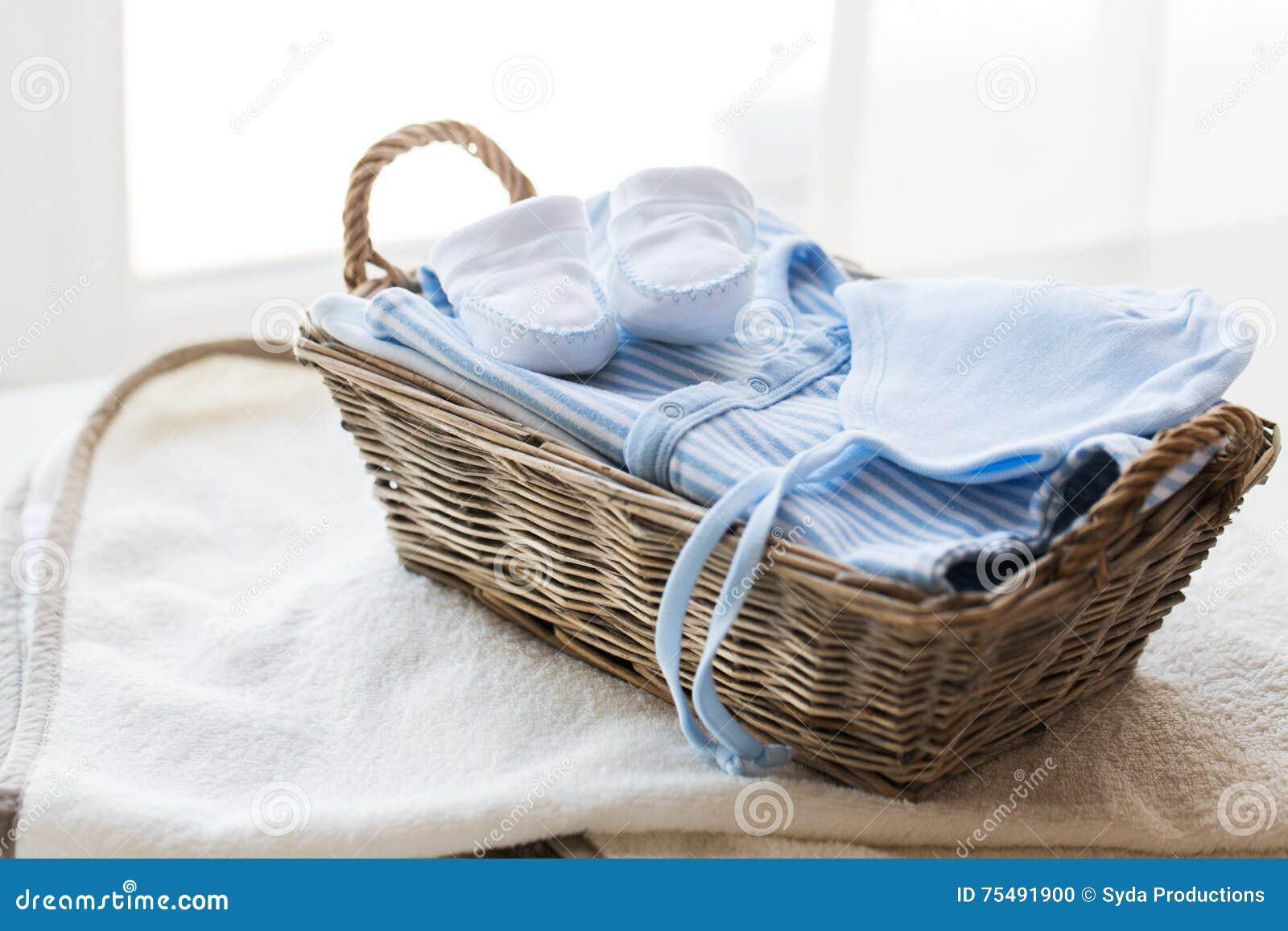 Sluit omhoog van babykleren voor pasgeboren jongen in mand