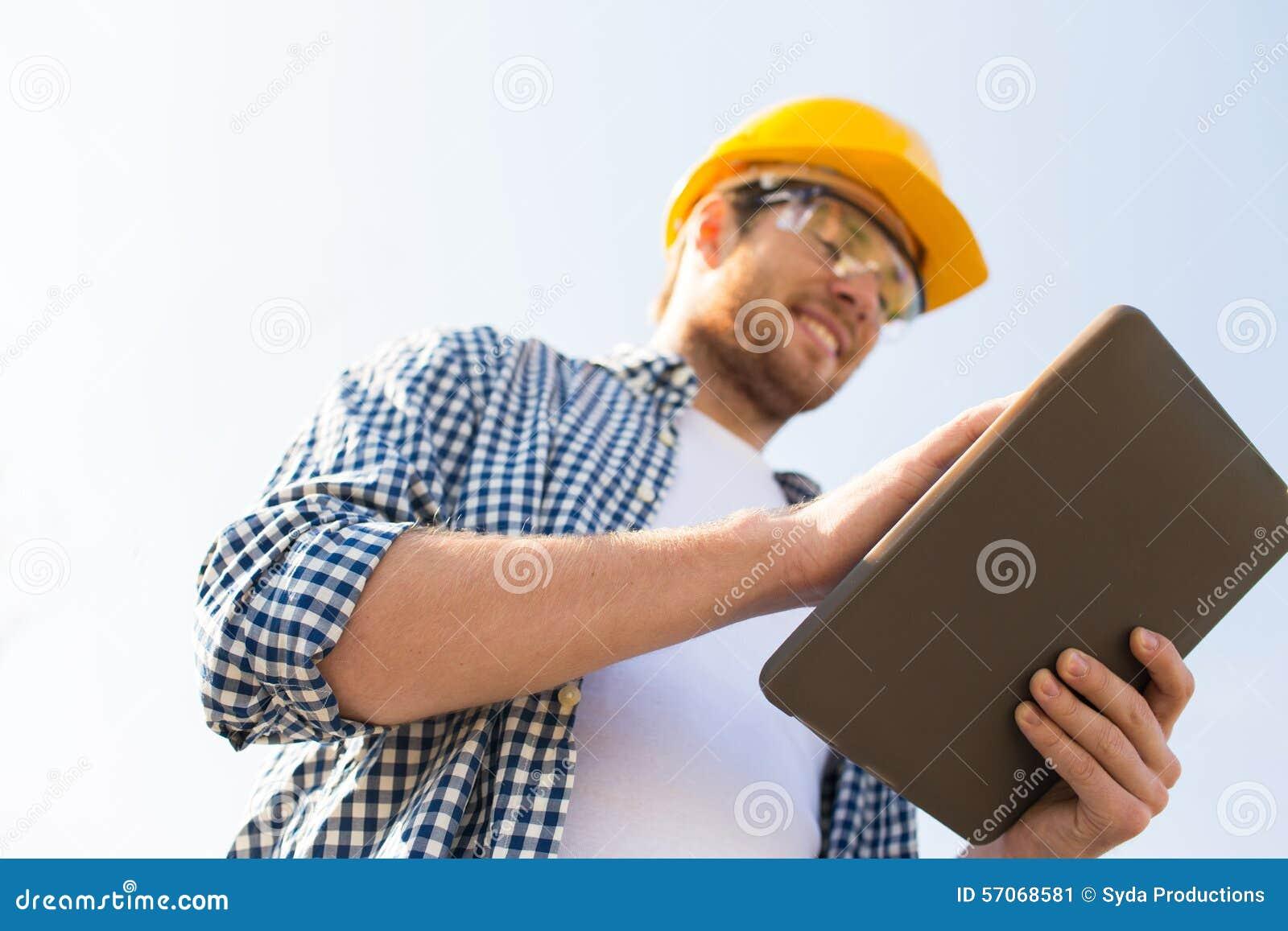 Sluit omhoog van bouwer in bouwvakker met tabletpc
