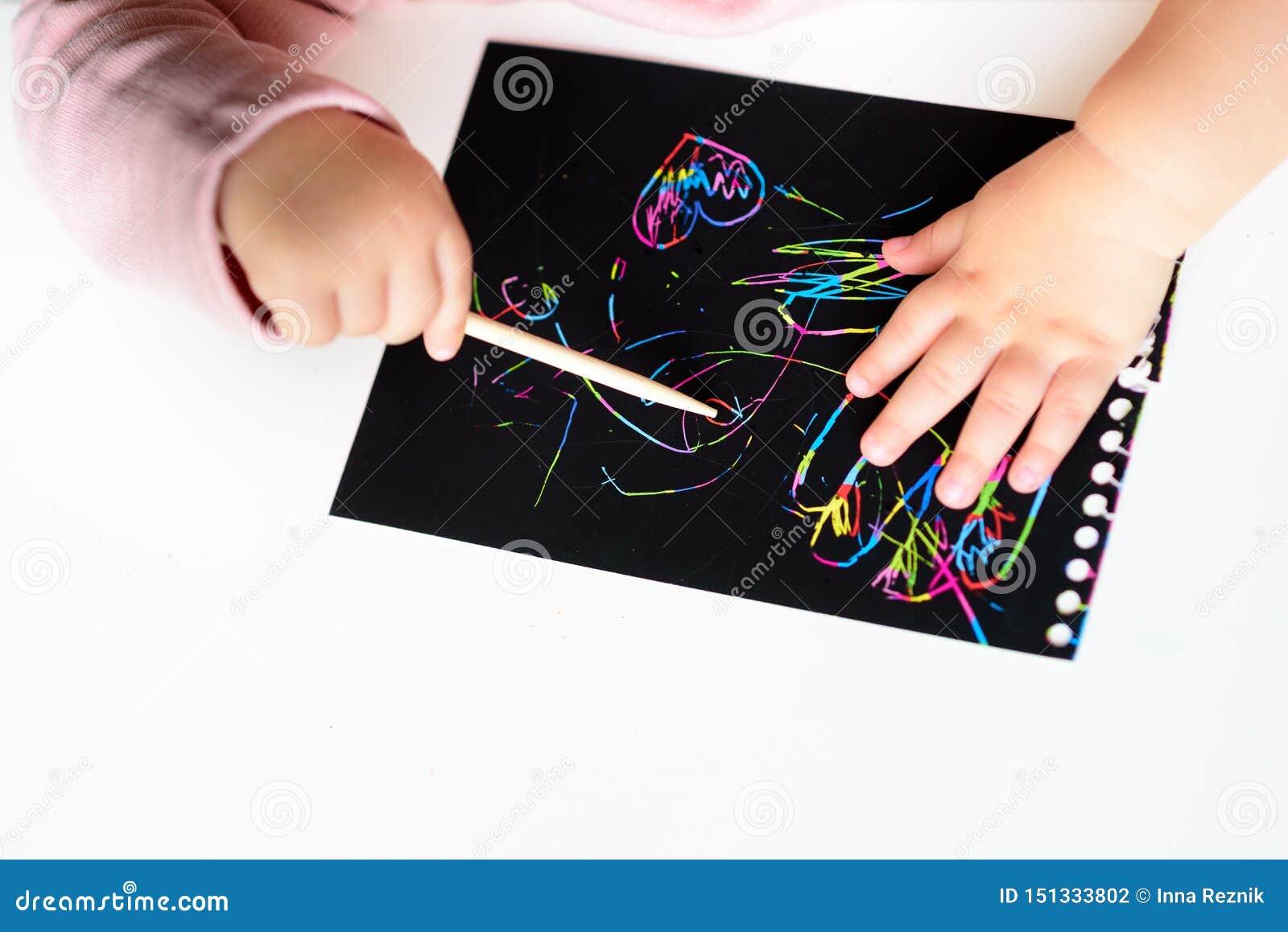 Sluit omhoog van de handen van een klein kind die op magisch kras het schilderen document met tekeningsstok trekken