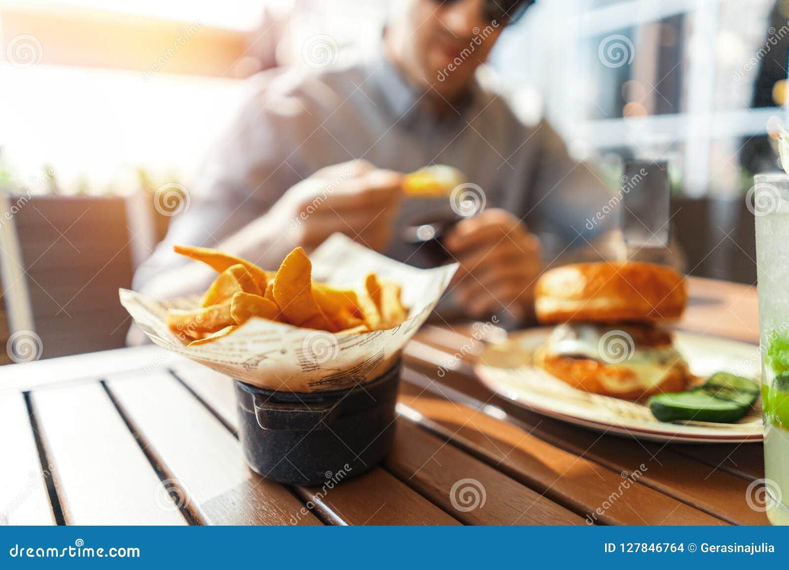 Sluit omhoog van de jonge aantrekkelijke mens die frieten en hamburger eten bij straatkoffie
