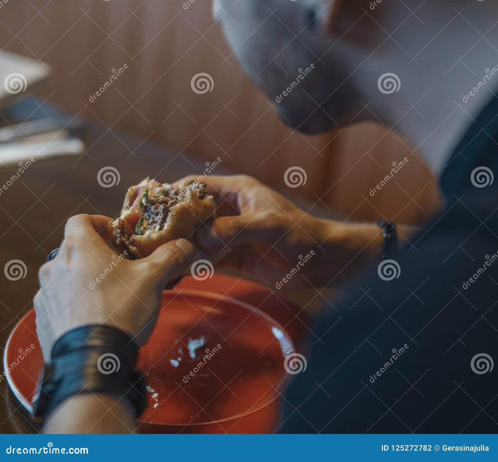 Sluit omhoog van de jonge aantrekkelijke mens die hamburger en frieten eten bij koffie