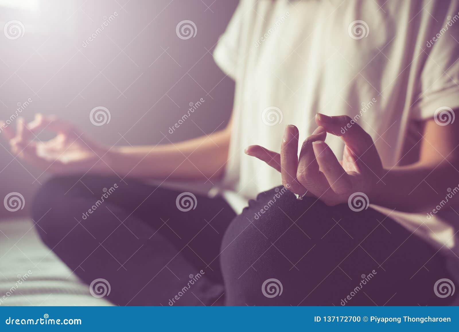 Sluit omhoog van de praktijkenyoga en meditatie van de handvrouw op de lotusbloemhouding