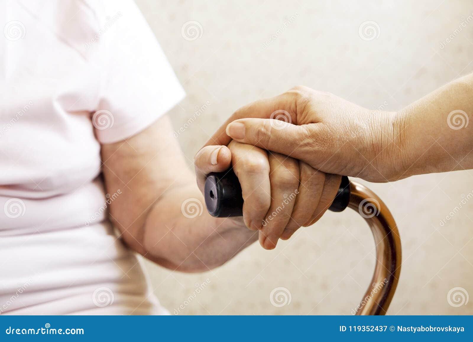 Sluit omhoog van de rijpe handen van de vrouw & van de verpleegster Gezondheidszorg die, verpleeghuis geven Ouderlijke liefde van