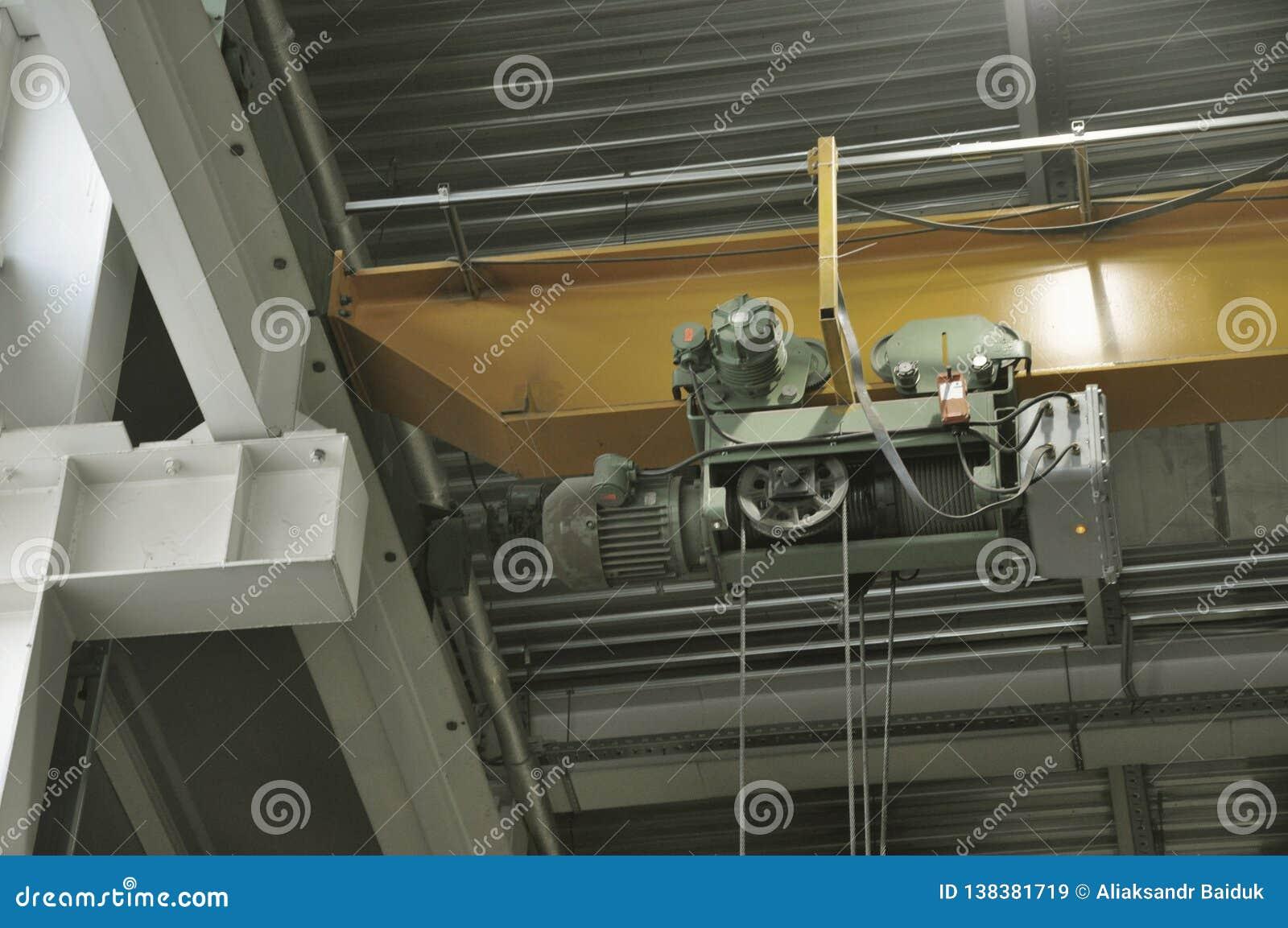 Sluit omhoog van een binnenfabrieks luchtkraan op een gele straal
