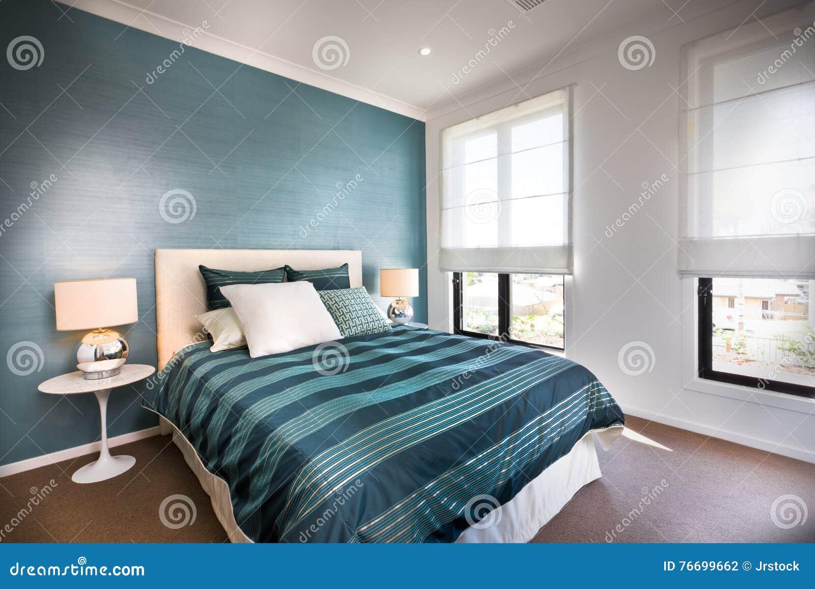 Decoratie Slaapkamer Muur : Sluit omhoog van een blauwe decoratieve slaapkamer met witte muren