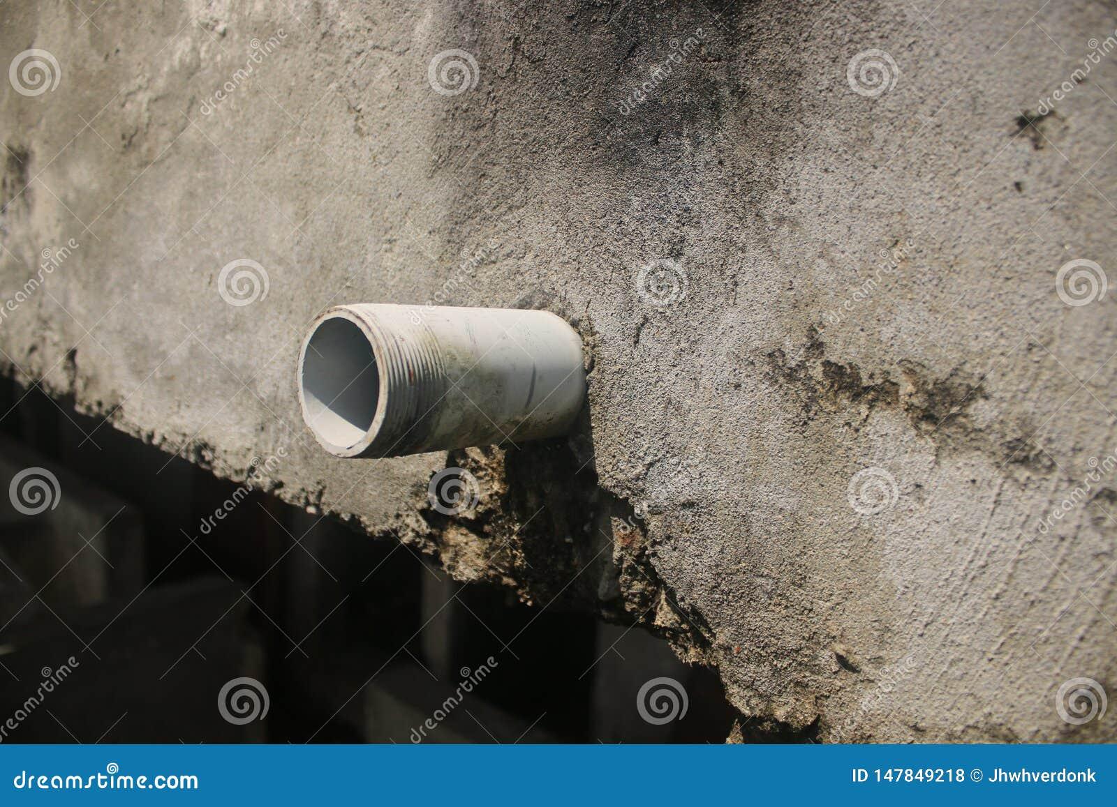 Sluit omhoog van een drainagepijp die uit een vuile grijze muur plakken