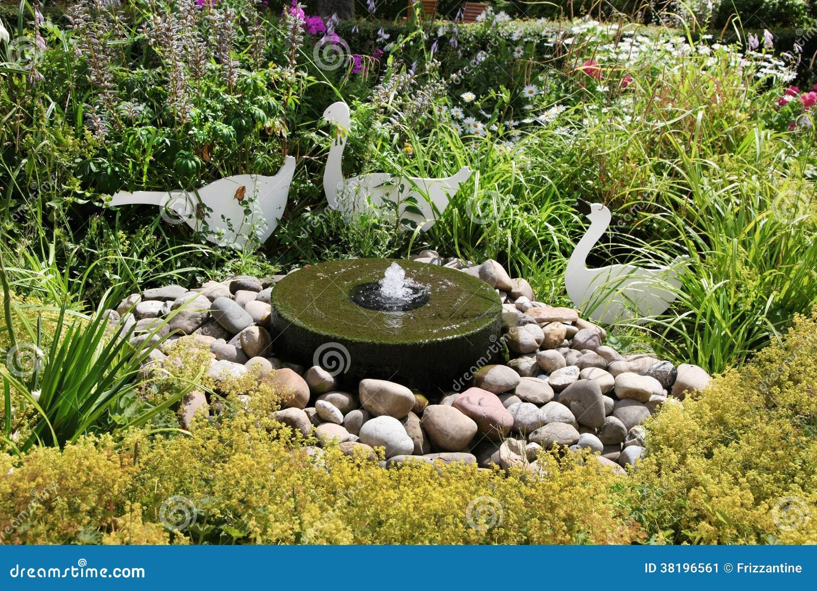 sluit omhoog van een fontein met stenen en installaties bij een tuin stock afbeelding