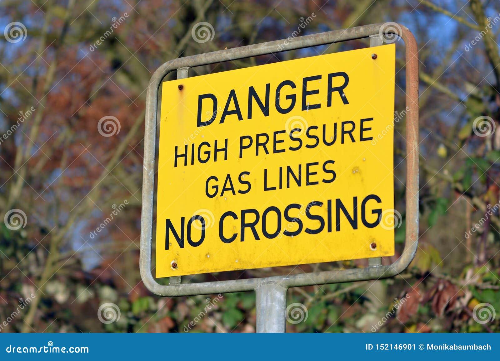 Sluit omhoog van een geel openluchtwaarschuwingsbord zeggend dager hoge drukgasleiding geen kruising