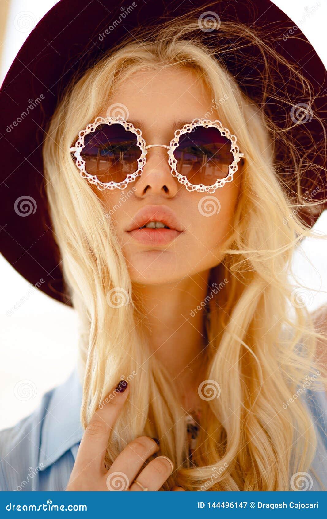 Sluit omhoog van een sensueel blonde met ronde bloemenzonnebril, grote lippen, de golvende haar en hoed van Bourgondi?, bekijkend