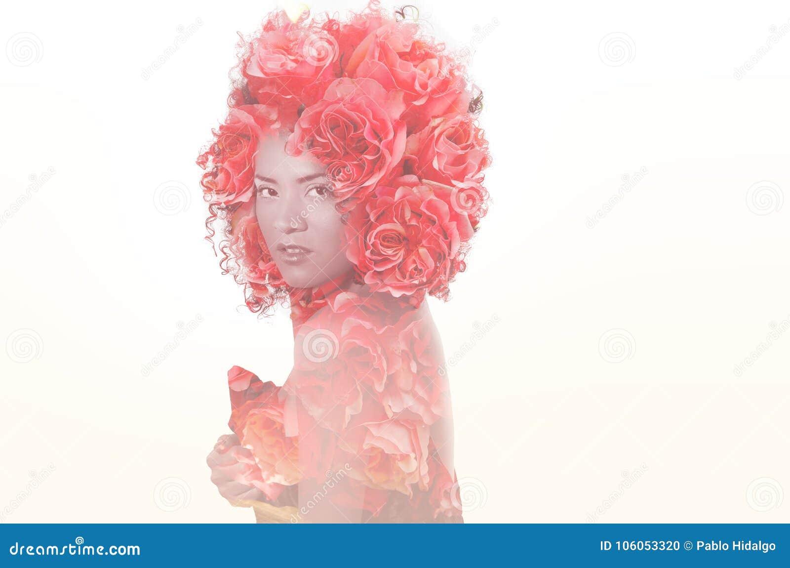 Sluit omhoog van een sexy mooi Afrikaans Amerikaans meisje met een afrokapsel, met doble blootstelling van bloemen in haar hoofd