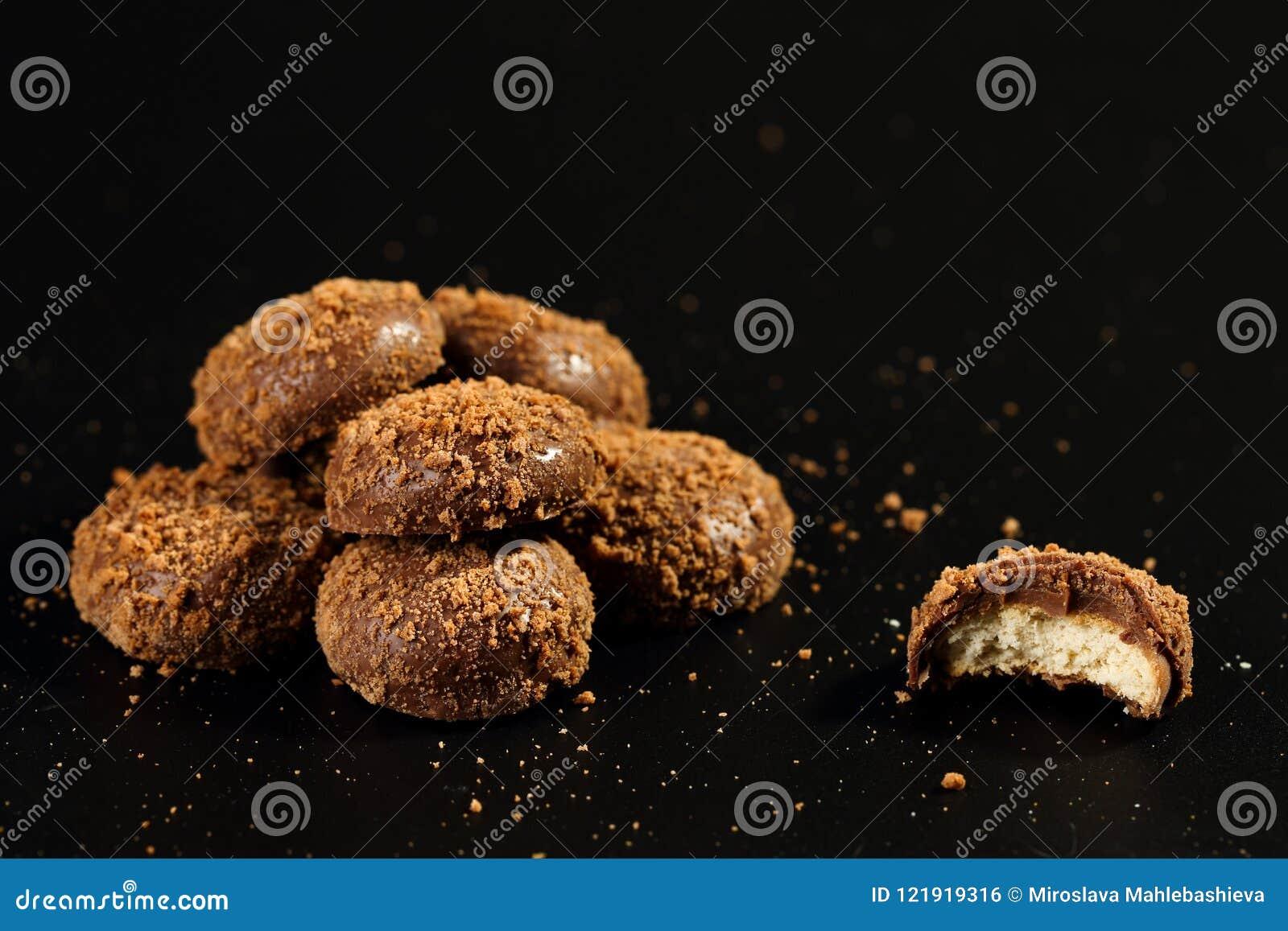 Sluit omhoog van een stapel en half gebeten heerlijke knapperige die karamelkoekjes met melkchocola en koekjesdeeltjes met een la